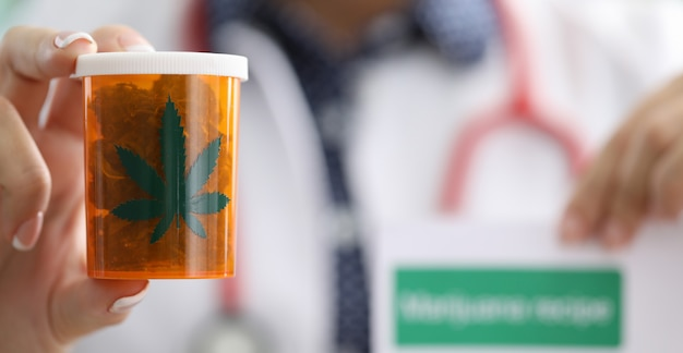 Close up, doctors hands holding jar marijuana