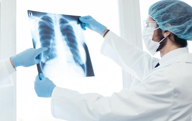 확대. 폐의 x- 레이를 논의하는 보호 마스크를 착용 한 의사. 건강 관리의 개념입니다.