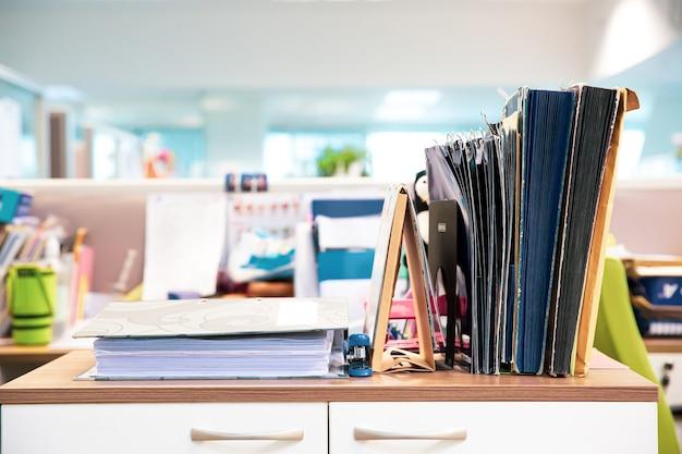 Close-up document folders stack on office desk.