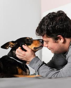Chiuda sul cane che lecca l'uomo sul viso