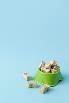 Primo piano su prelibatezze per cani a forma di osso sulla ciotola del cibo