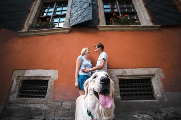 Close-up of dog with romantic couple in background