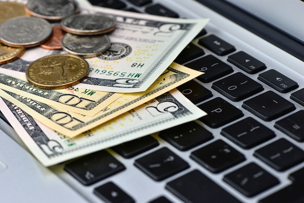 Close up of dollar banknotes and coins on laptop keyboard, online business concept