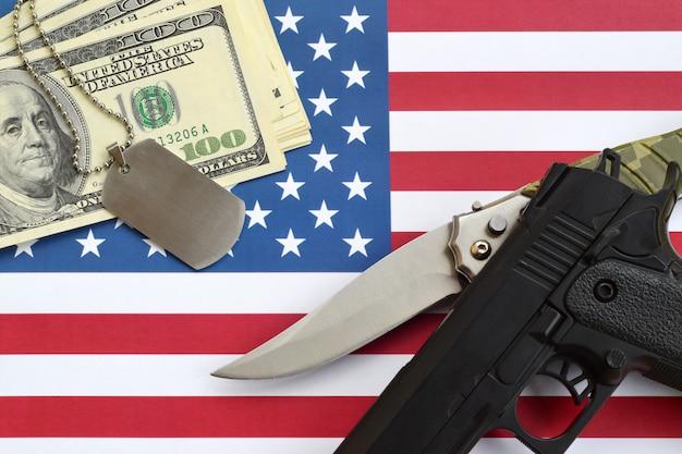 アメリカ合衆国の国旗に武器と軍事バッジでドルのお金を閉じます。軍事力、資金調達、国家奉仕のコンセプト