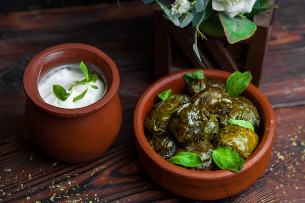 Close up dolma grape leaves stuffed with meat and rice with sour cream sauce on a dark wooden table. eastern european and asian traditional cuisine.