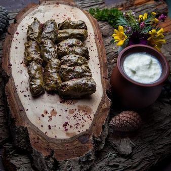 Close up dolma grape leaves stuffed with meat and rice with sour cream sauce on a dark wooden table. eastern european and asian traditional cuisine