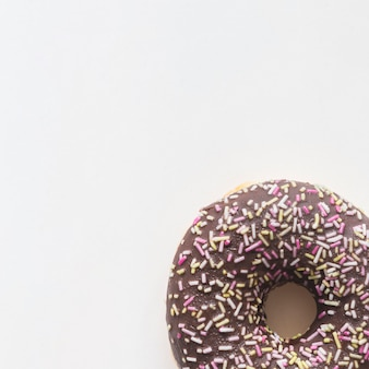 Close-up of donut with sprinkles on white background