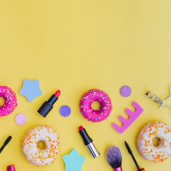 Close-up of donuts; lipstick; eyelash curler; makeup brush and toe divider on yellow background