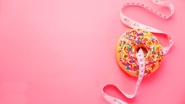 Close up of donuts and measurement tape on pink background.
