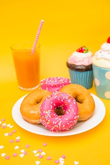 Close-up of donuts, muffins and glass of juice