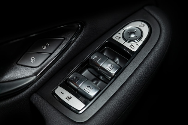 Close up of a door control panel in a new modern car. arm rest with window control panel
