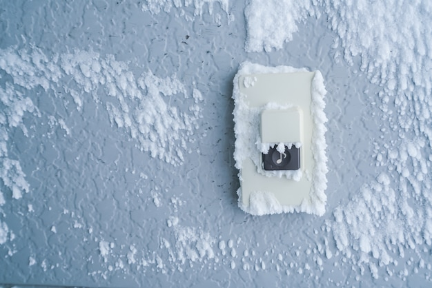 Close-up doorbell button cover with white snow .