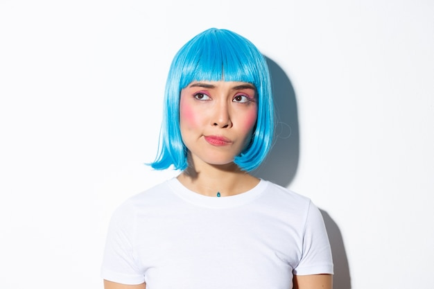 Close-up of doubtful frowning asian girl in blue wig, looking with disbelief at upper left corner, standing.