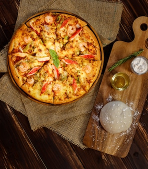 Close up on dough, olive oil, powder and rolling pin for making homemade seafood pizza with shrimp, crab sticks, bell peppers on sackcloth and wooden table. food concept.