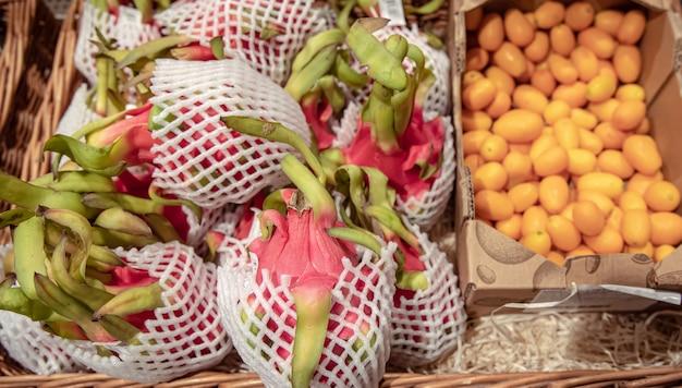 Primo piano di frutta del drago e kinkan su un bancone del supermercato.