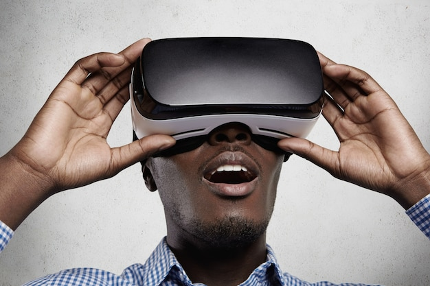 Close up of drak-skinned man in checkered t-shirt and 3d headset, watching something fascinating and surprising while experiencing virtual reality.