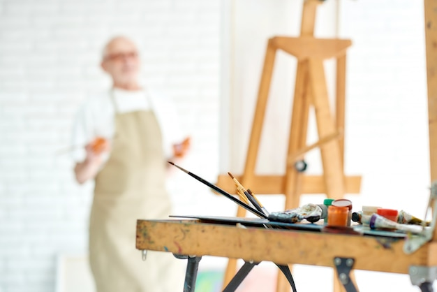 Close up of drawing instruments and tools, artist watercolors brushes and easel with male artist