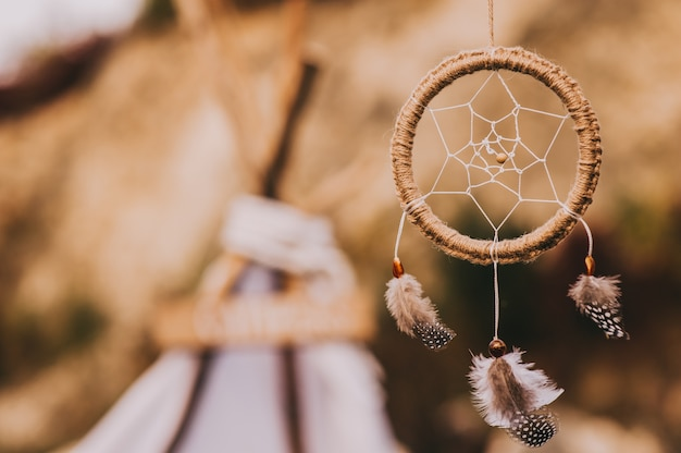 Close up of dream catcher on blurred background in evening sun light in vintage colors.