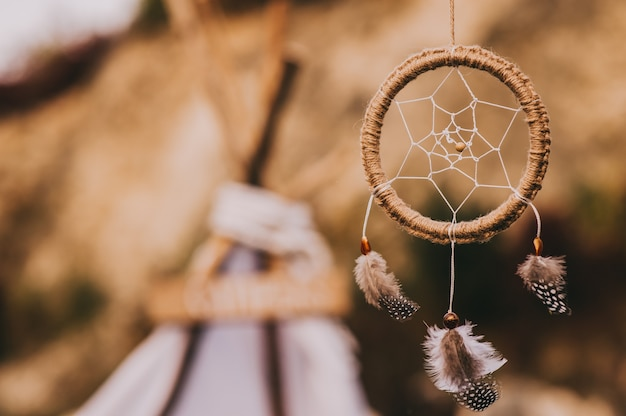 Close up of dream catcher on blurred in evening sun light in vintage colors.