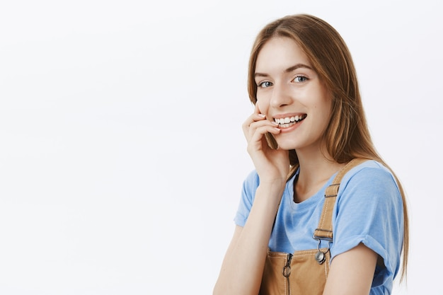 Close-up of dreamy beautiful young girl smiling, touching face gently and looking  coquettish