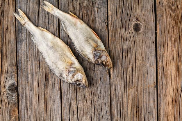 어두운 나무 배경에 근접 말린 된 생선