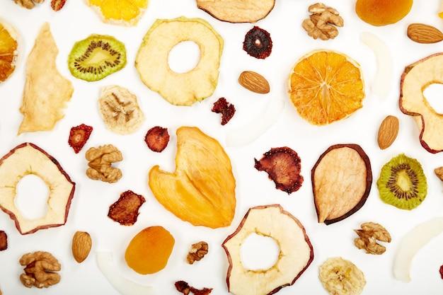 Primo piano di fragole secche, mandorle, albicocche secche, uvetta, noci, mele secche e kiwi su sfondo bianco. concetto di frutta secca assortita sana biologica per spuntini.