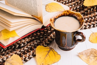 Close-up drink and leaves near scarf and book