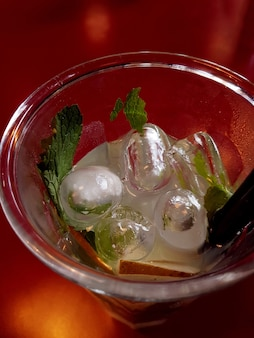 Close up of a drinking glass with ice and mint. top view