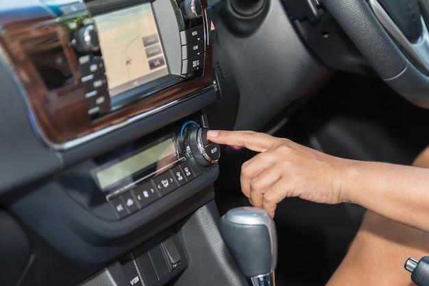 차에서 드라이버 핸드 프레스 에어컨 버튼을 닫습니다