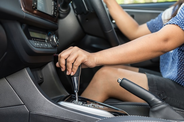 Close up driver left hand shifting the gear stick in car