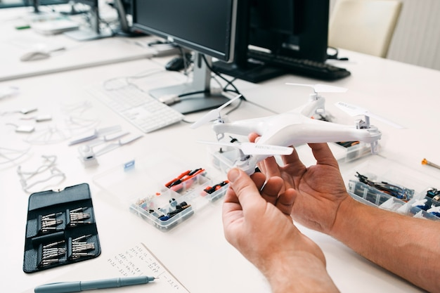 Close-up of drone in repairman hands, electronic toy repair shop. electrician workplace with fixed unmanned aerial vehicle. business, electronic construction, modern technology concept