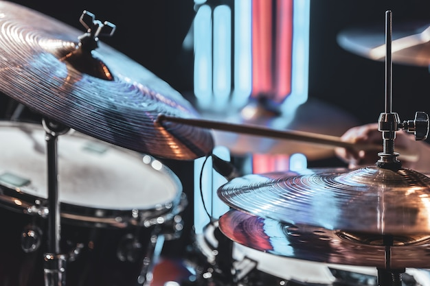 Close-up of drum cymbals as the drummer plays with beautiful lighting on a blurred background.