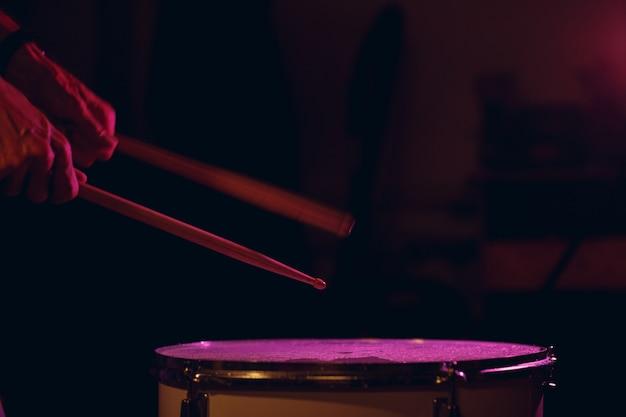 ドラムスティックをクローズアップドラム表面でヒットビートリズムを叩き、長時間露光モーションブラーで水滴を飛ばします