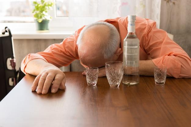 Закройте вверх по пьяному лысому пожилому человеку, вздремнув на деревянном столе с водкой и маленькими стаканами.