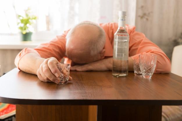 Крупным планом пьяный старый лысый мужчина, опираясь на деревянный стол с водкой, держа небольшой стакан