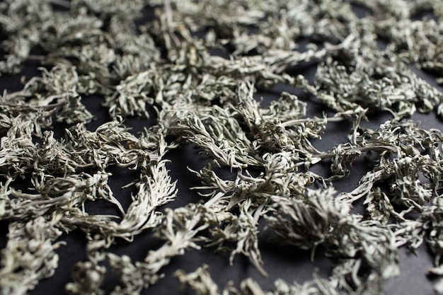 Close-up of dry sagebrush on black table. natural abstract background.