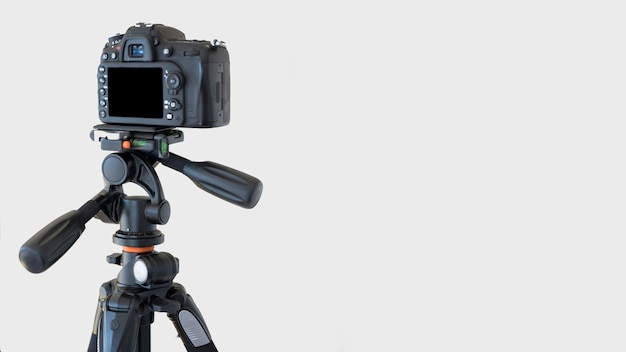 Close-up of a dslr camera on a tripod over white background