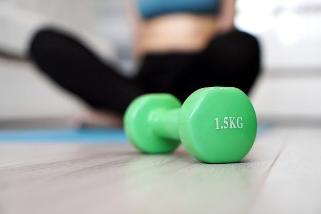 Close up of dumbbell and woman stretching in blurred