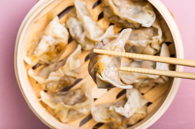 Close-up dumpling in chopsticks