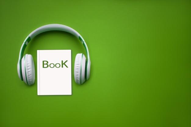 근접 이어폰 및 녹색 배경에 오디오북입니다. 오디오, 들어보세요. 오디오북 개념입니다.