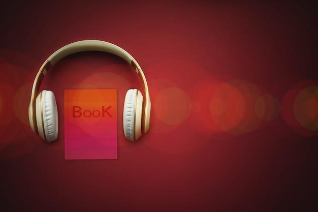보케가 있는 빨간색 배경에 클로즈업 이어폰 및 오디오북. 오디오, 들어보세요. 오디오북 개념입니다.