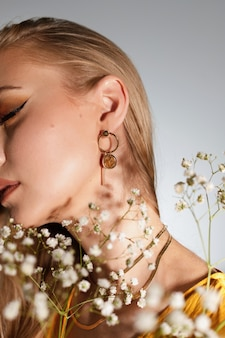 Close-up of earrings on the ear of a blonde model with a bouquet of flowers. fashion blogger