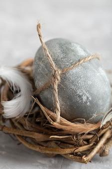 Primo piano dell'uovo di pasqua nel nido dell'uccello con la piuma