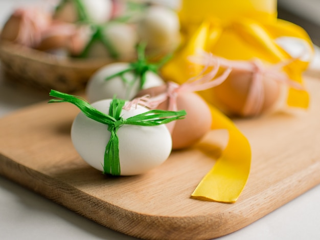 Close-up of easter eggs tied with ribbon on white background