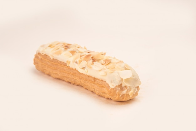 Close up of eclair with white cream and nuts isolated over white
