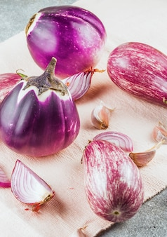 Close-up of eggplants; garlic cloves and onions on cloth