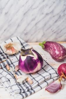 Primo piano di melanzane; cipolla; spicchi d'aglio e tessile motivo a scacchi sulla superficie in legno