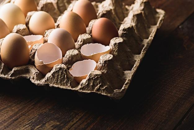 갈색 배경에 친환경 골판지 상자에 달걀 껍질로 계란을 닫습니다.