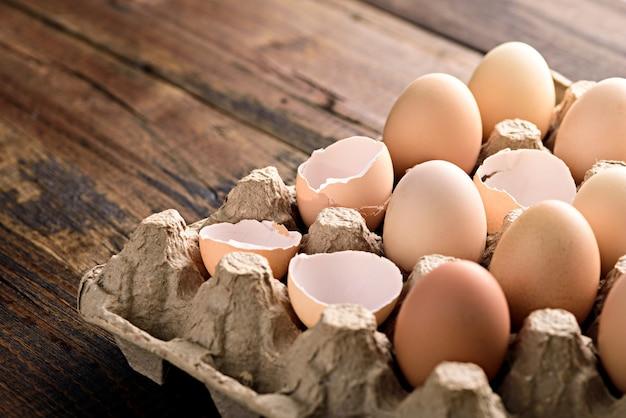 갈색 배경에 친환경 골판지 상자에 껍질과 계란을 닫습니다