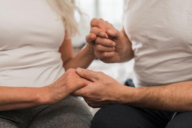 Close-up elder couple holding hands